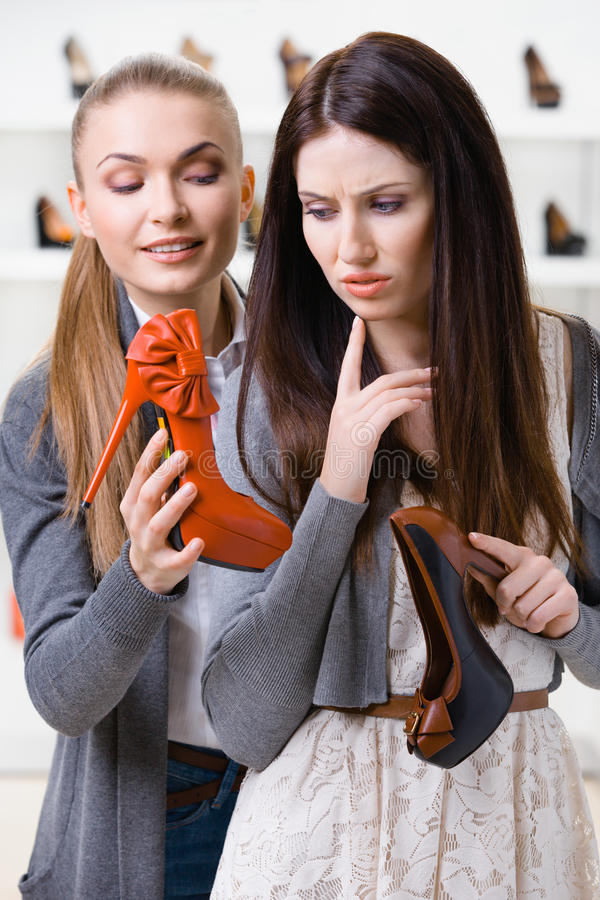 Shop assistant offers shoes for the customer royalty free stock image