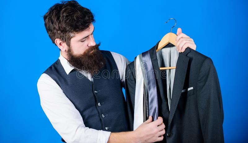 Shop assistant or personal stylist service. Matching necktie with outfit. Man bearded hipster hold neckties and formal stock image