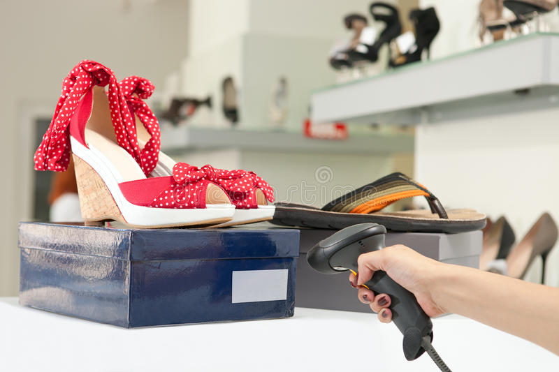 Shop assistant scanning code on shoe box stock images