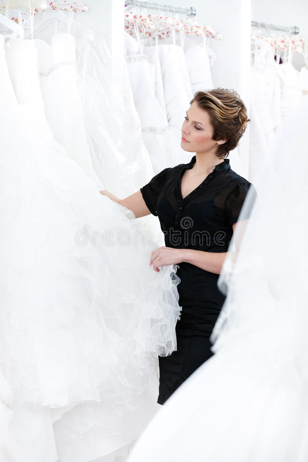 Shop assistant try to make the best dress recommendation stock image