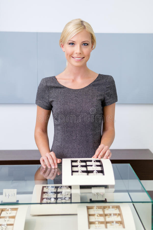 Shop assistant at the window case with rings stock photo