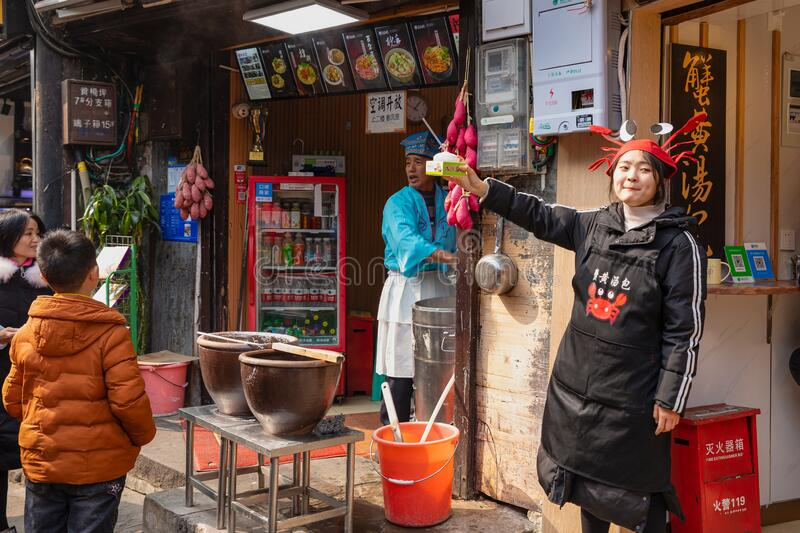 Shop assistants bartering their goods at Ciqikou stock photography
