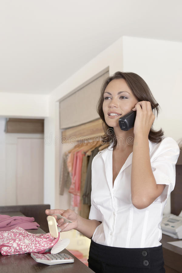 Download Shop Attendant on Phone stock image. Image of indoors - 25672257
