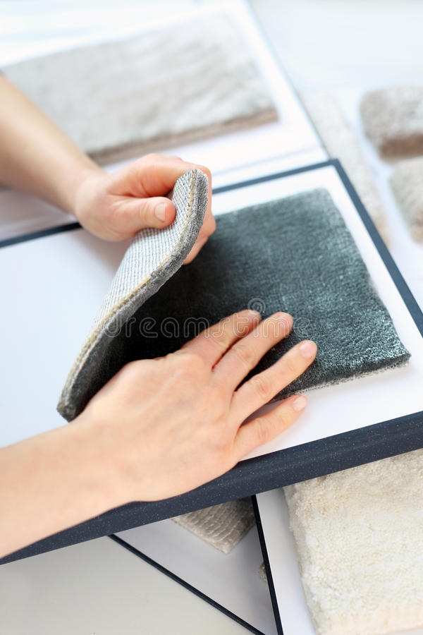 Shop carpets. Woman in shop with carpets chooses carpet probe royalty free stock images