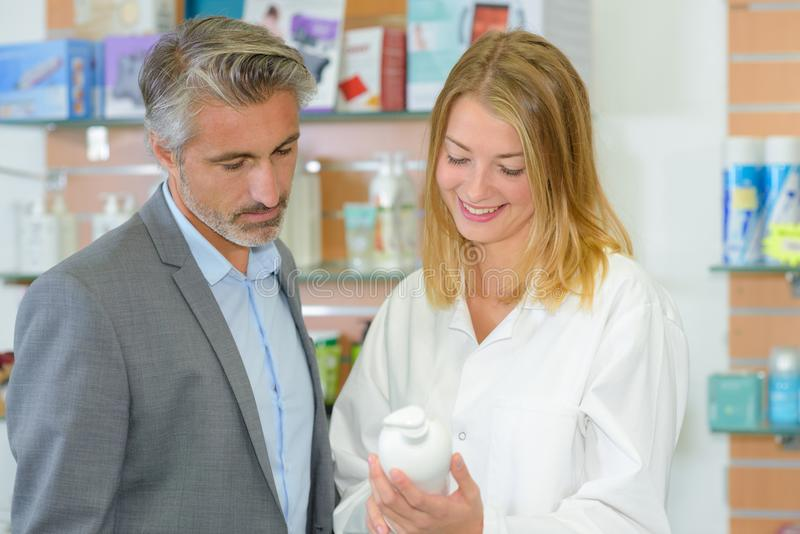Shop clerk recommending product for male customer stock photography