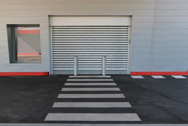 Shop closed with the metal gate pulled down. It is in a modern building made of aluminum cladding, with a street and crosswalk stock images