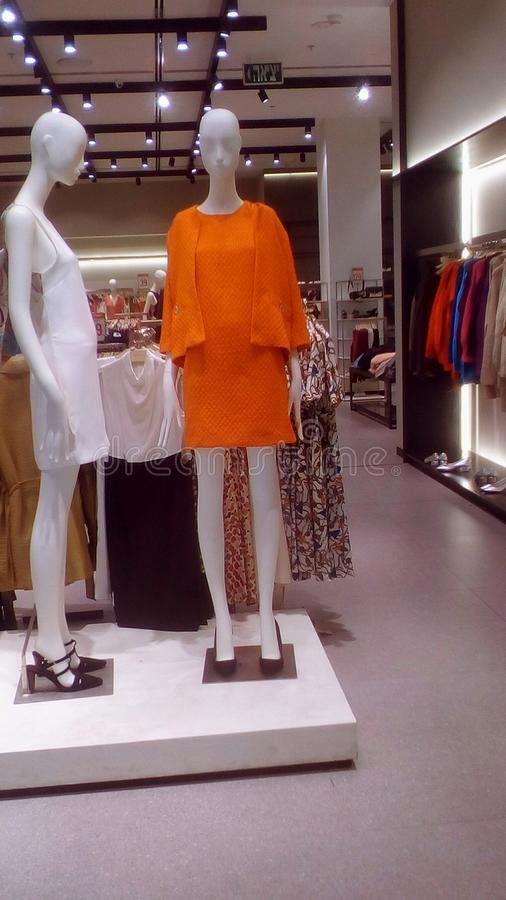 In shop. It is a horizont view from big luxury fashion shop in mall.Appear two women mannequin on podium which wear fashionable modern dresses and in the stock image