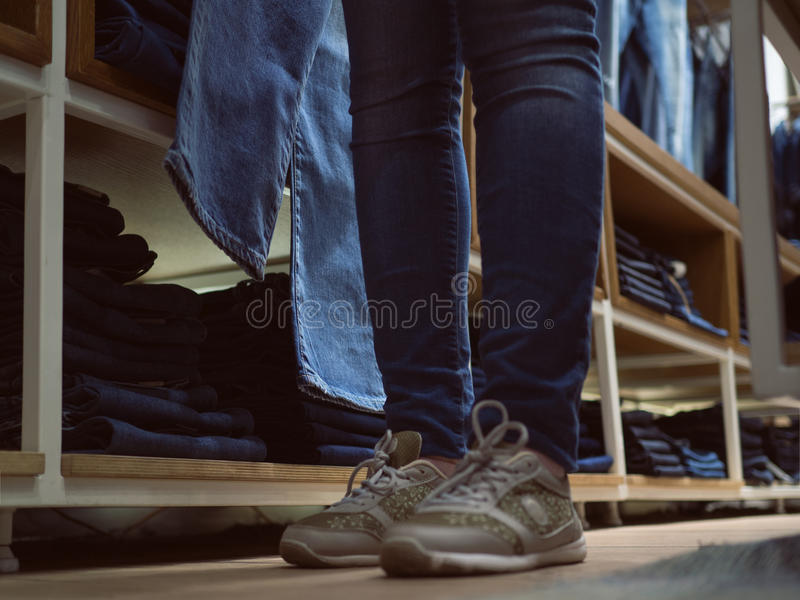 Shop of jeans clothes. Legs girl in jeans in denim clothing stor royalty free stock photography