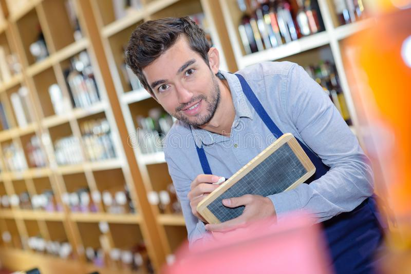 Shop vendor writing on blackboard royalty free stock photo