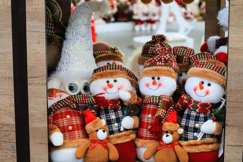 Shop window with Christmas and New Year s toys and decorations. Funny snowmen in hats on a shelf of a toy store. Festive winter. Trade, fair in a shopping stock images