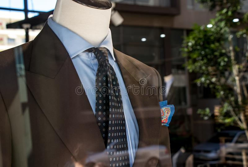 Shop window of mens tailor shop showing a mannequin in a brown tailored suit and blue tie stock photo