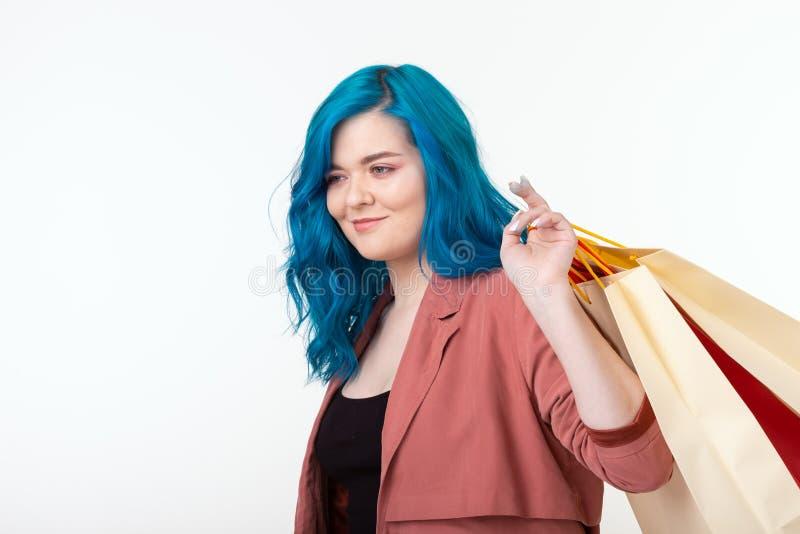 Shopaholic και καταναλωτών έννοια πώλησης, - όμορφο κορίτσι με την μπλε τρίχα που στέκεται με τις τσάντες αγορών στο άσπρο υπόβαθ στοκ φωτογραφίες με δικαίωμα ελεύθερης χρήσης