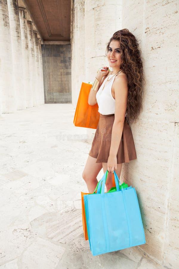 Shopaholic 购物爱 有袋子的美丽的愉快的妇女 免版税库存图片
