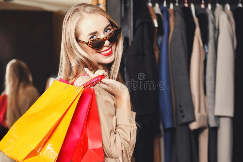 Shopaholic assez blond souriant avec des paniers photos libres de droits