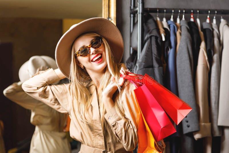 Shopaholic bastante rubio que ríe con los panieres fotos de archivo libres de regalías