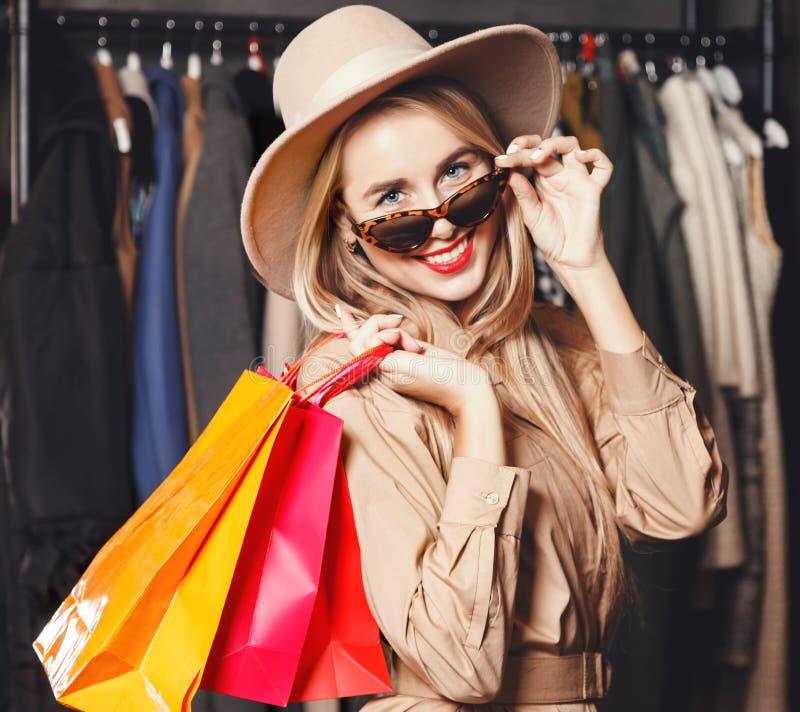 Shopaholic bastante rubio que sonríe con los panieres imagen de archivo libre de regalías