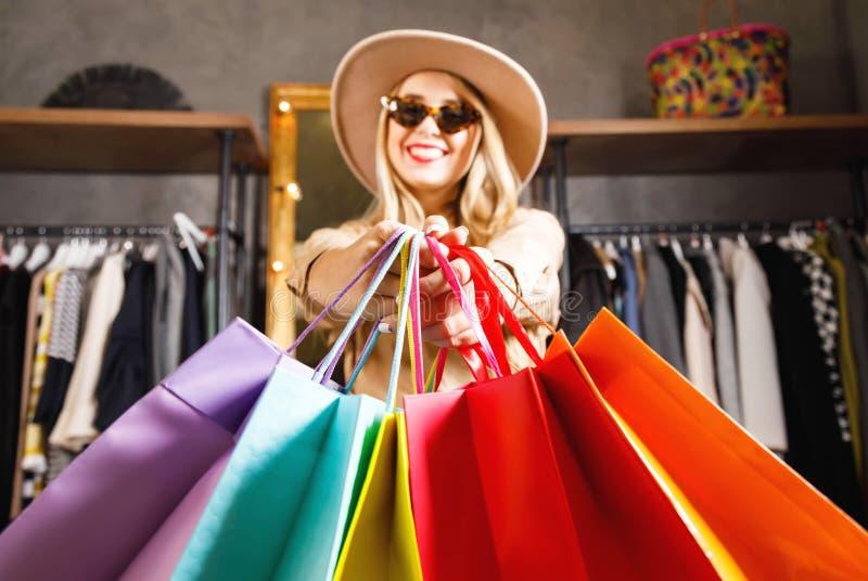 Shopaholic bastante rubio que sonríe con muchos panieres coloridos fotos de archivo