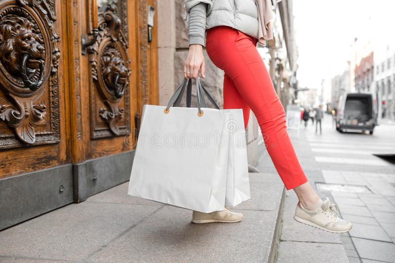 Shopaholic beautiful happy woman goes shopping in the city. Young girl in red pants and a lot of grey paper bags her royalty free stock photos