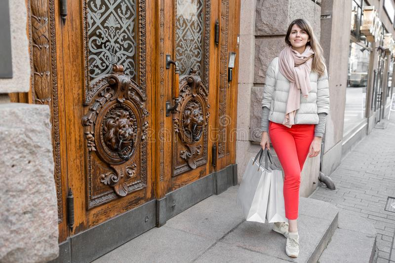 Shopaholic beautiful happy woman goes shopping in the city. Young girl in red pants and a lot of grey paper bags her stock photo
