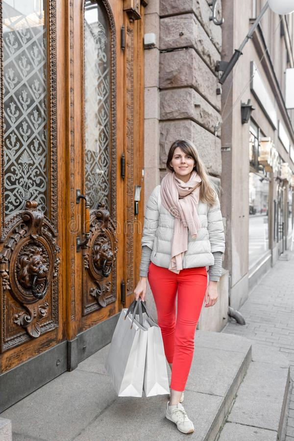 Shopaholic beautiful happy woman goes shopping in the city. Young girl in red pants and a lot of grey paper bags her royalty free stock image
