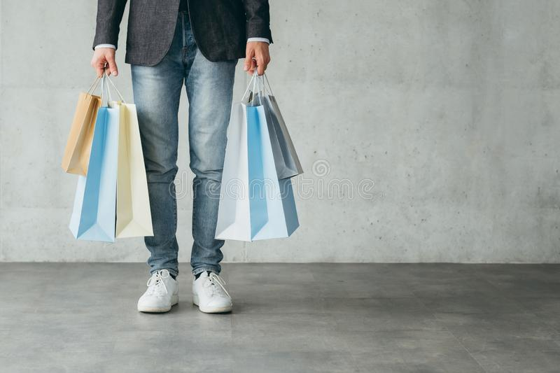 Shopaholic consumerism multiple bags man hands. Shopaholic and consumerism concept. multiple bags with goods from stores in man hands royalty free stock photography