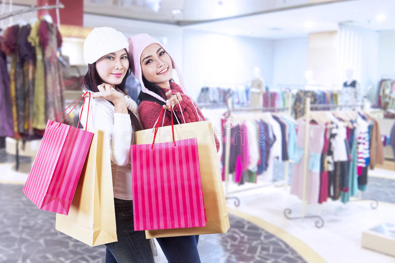Shopaholic friends holding bags in the mall. Two friends who love shopping are holding bags in front of the mall stock photo