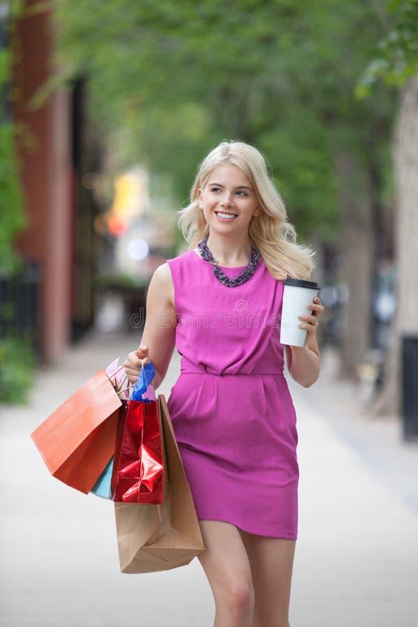 Shopaholic kvinna med den disponibla kaffekoppen fotografering för bildbyråer