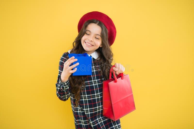 ??shopaholic r 法国贝雷帽的愉快的女孩 有礼物盒的孩子在黄色背景 小女孩孩子 库存照片