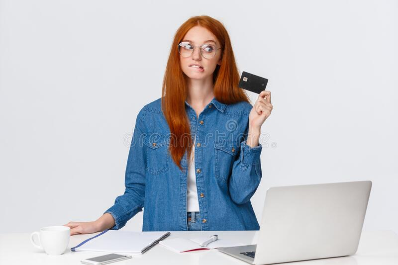 Shopaholic trying hold herself from buying new things during online discounts, biting lip eager waste some money royalty free stock photography