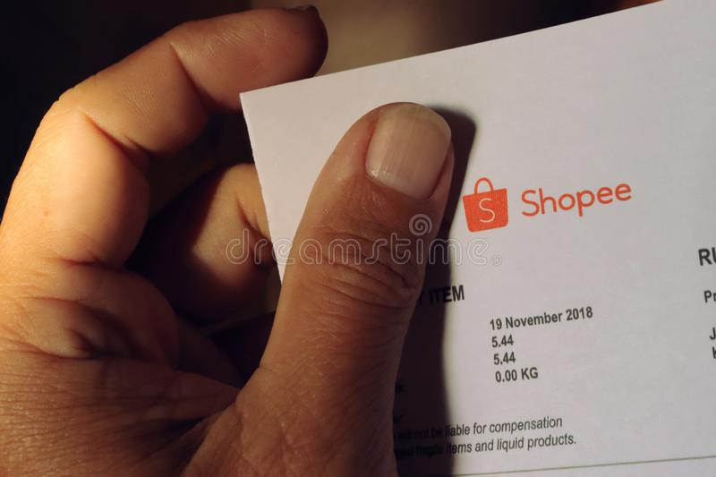 Shopee Logo On Delivery Note. Shopee delivery note that is held on the left hand. The Shopee logo is clearly visible while the Pos Laju logo is obstructed by the stock photo