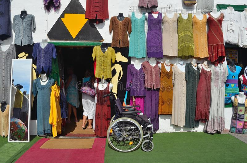 Shopfront with colorful garments hanging on wall with Wheelchair left outside and mirror. TEGUISE, LANZAROTE, SPAIN - NOVEMBER 20, 2016: Shopfront with colorful stock images