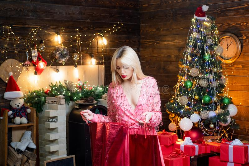 Shoping bag, sale, christmas discounts. Woman in evening dress over home Christmas tree background. New year eve stock photo