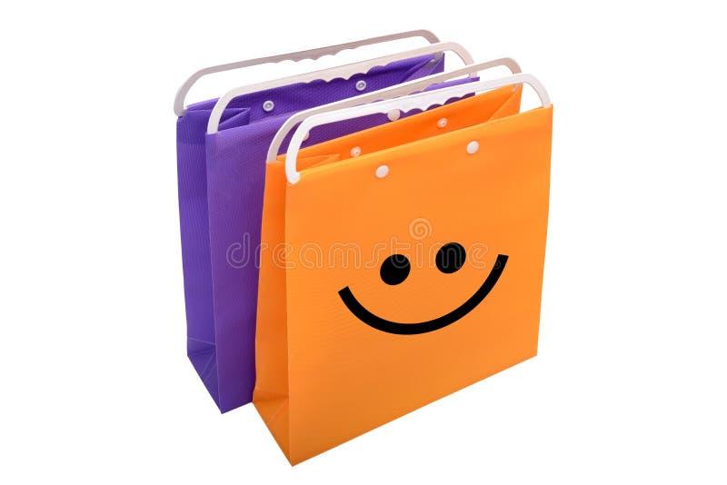 Shoping-Tasche mit Lächelnikone auf weißem Hintergrund stockfotografie
