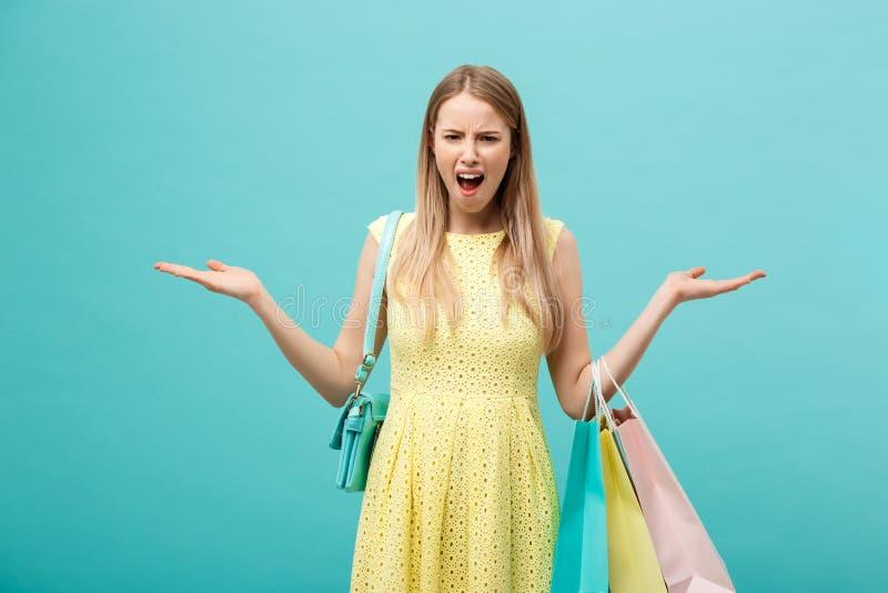 Shoping und Verkaufs-Konzept: schöne unglückliche junge Frau im gelben eleganten Kleid mit Einkaufstasche stockfotografie