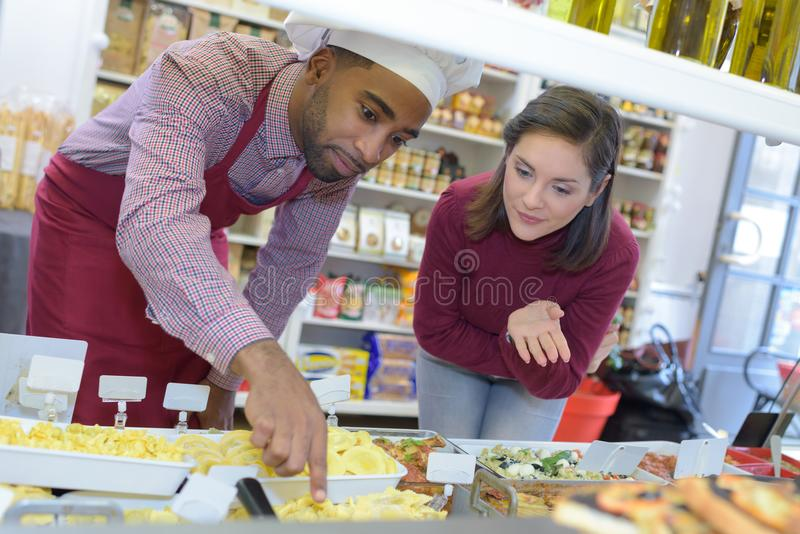 Shopkeeper gives pastry to woman royalty free stock images