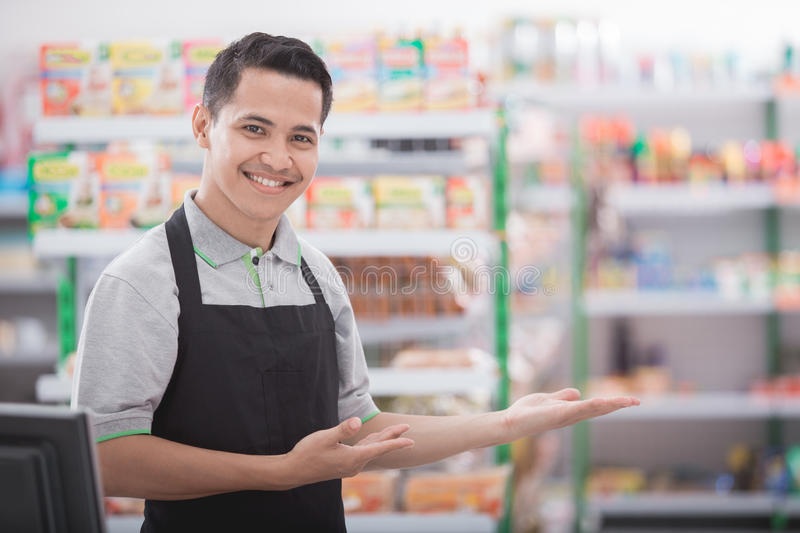 Shopkeeper in a grocery store. Portrait of a smiling shopkeeper in a grocery store welcoming customer stock photo