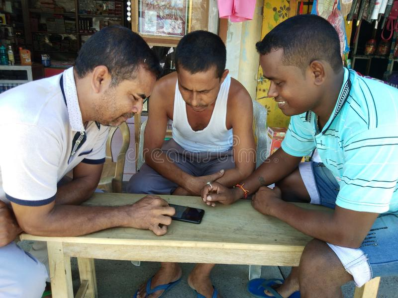 Shopkeepers playing Ludo game in mobile device in a hot summer day royalty free stock images