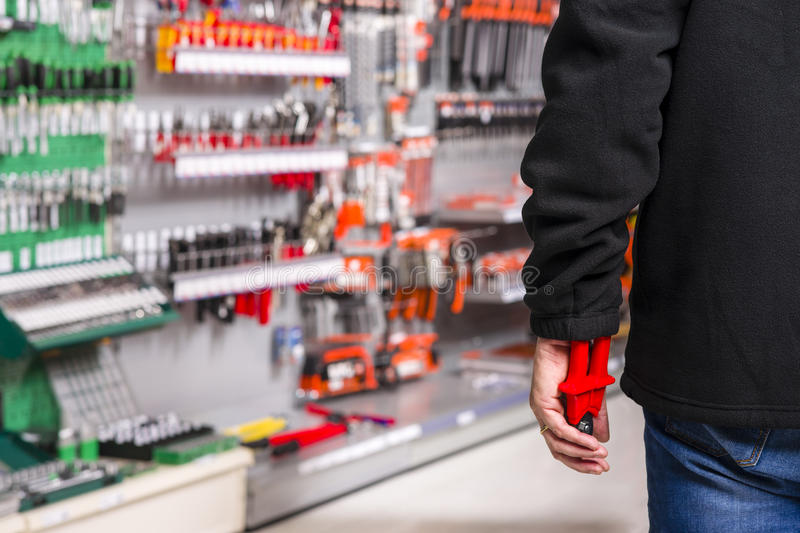Shoplifter at work. Male shoplifter stealing tools in a hardware store stock photo