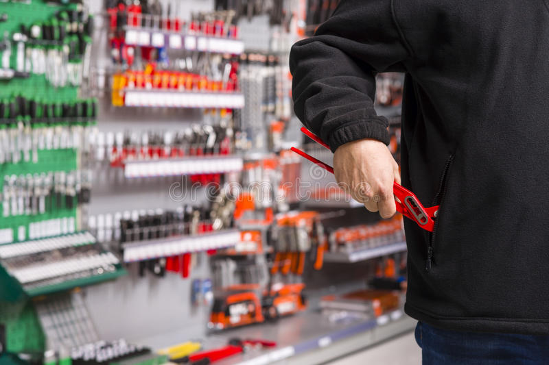 Shoplifter at work. Male shoplifter stealing tools in a hardware store stock photography