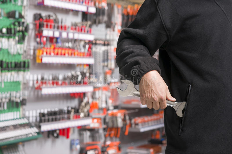 Shoplifter at work. Male shoplifter stealing tools in a hardware store stock images