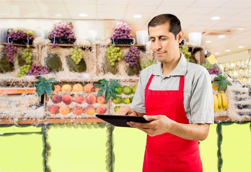 Shopman vérifiant le bulletin de livraison au greengrocery photo stock