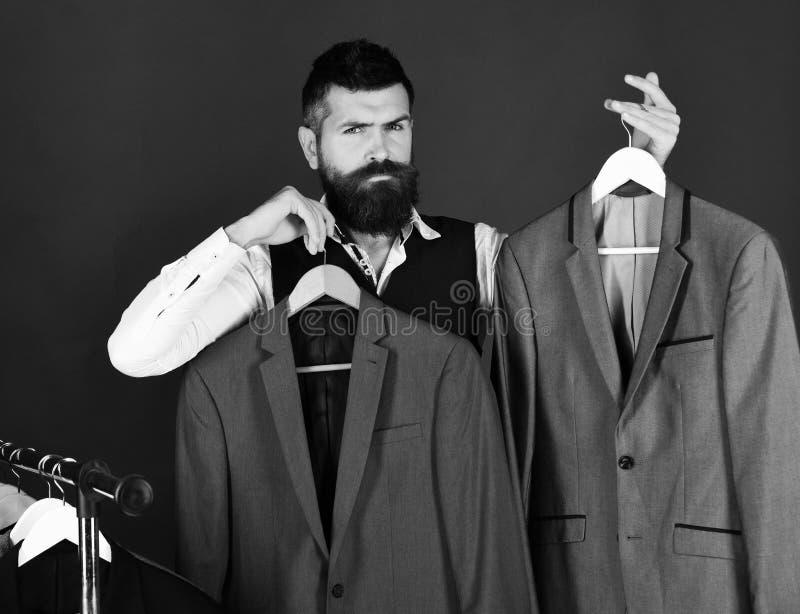 Shoppa assistenten, eller säljaren gör primaa near klädhängare royaltyfri foto