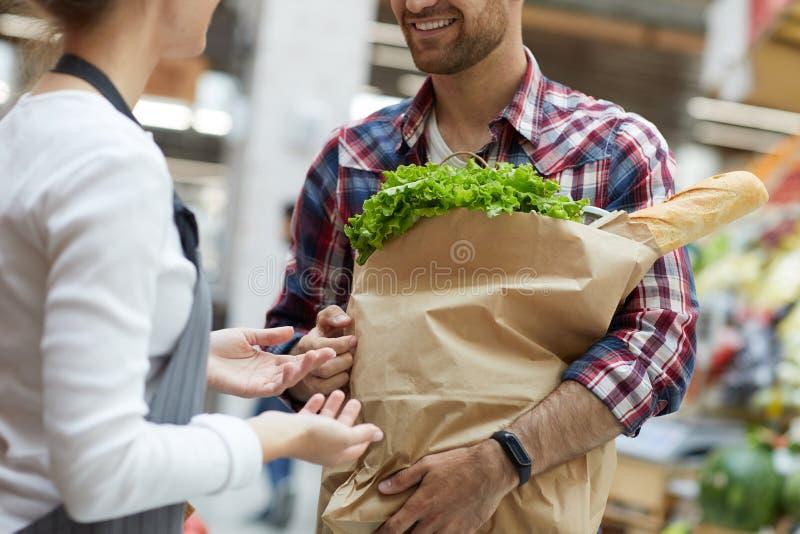 Shoppa assistenten som talar till kundcloseupen royaltyfria bilder
