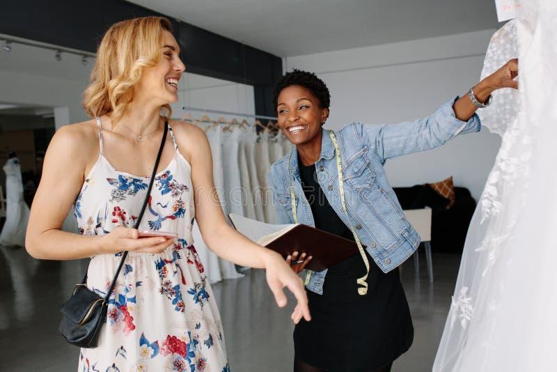 Shoppa assistenthjälp bruden, i att välja den brud- klänningen arkivbilder