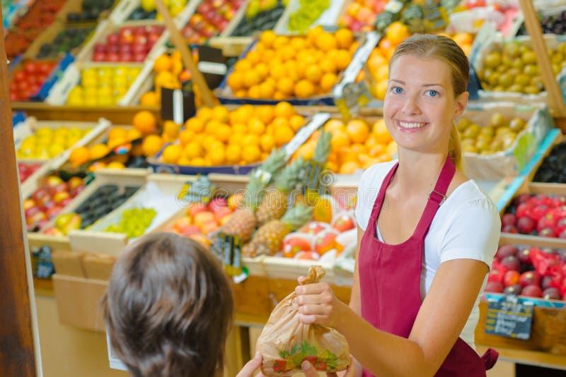 Shoppa assistentportionkunden i specerihandlare arkivfoton