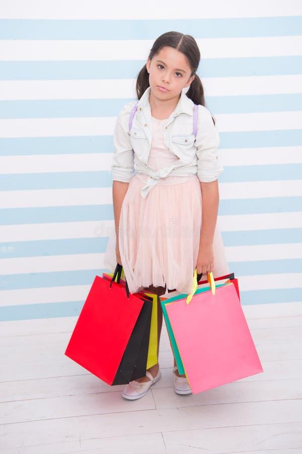 Shoppa att trötta evakuera aktivitet Barnet bär randig bakgrund för shoppingpåsar Ungeflickan spenderar dagköpsaker fotografering för bildbyråer