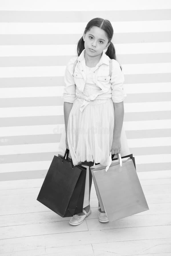 Shoppa att trötta evakuera aktivitet Barnet bär randig bakgrund för shoppingpåsar Ungeflickan spenderar dagköpsaker royaltyfri bild