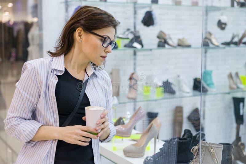 Shoppa den mogna kvinnan, kvinnlig som ser ett shoppafönster med skor som shoppar i galleria arkivfoton