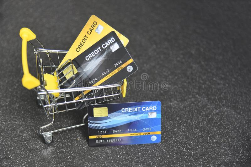 Shoppa direktanslutet med kreditkorten i en shoppa vagn på den mörka bakgrunden för online-betalning hemma fotografering för bildbyråer