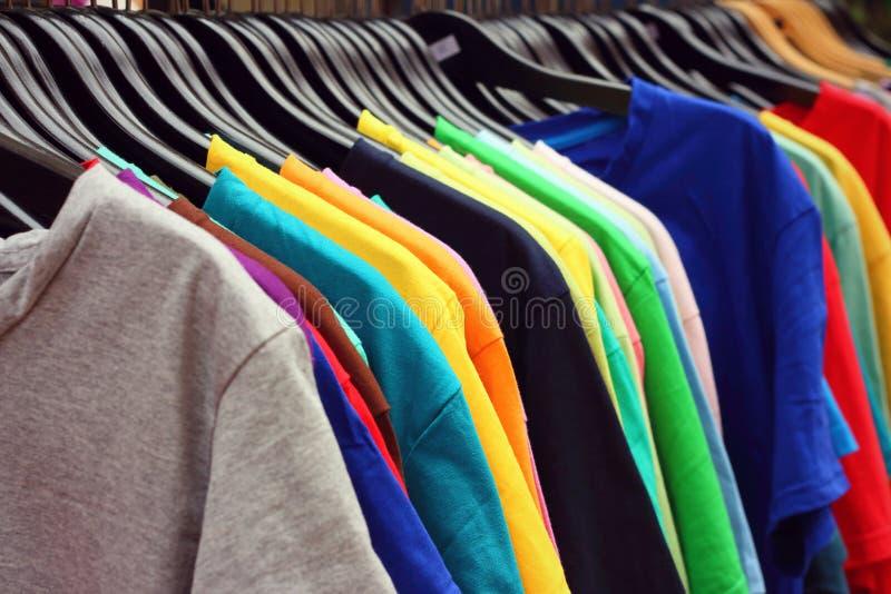 Shoppa färgrikt tyg för skjortor som hänger på en kugge arkivbilder